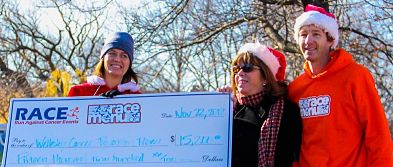 Wellesley Cancer Prevention Project board members Linda Griffith and Theresa Keresztes receiving  check from race organizer J. Alain Ferry