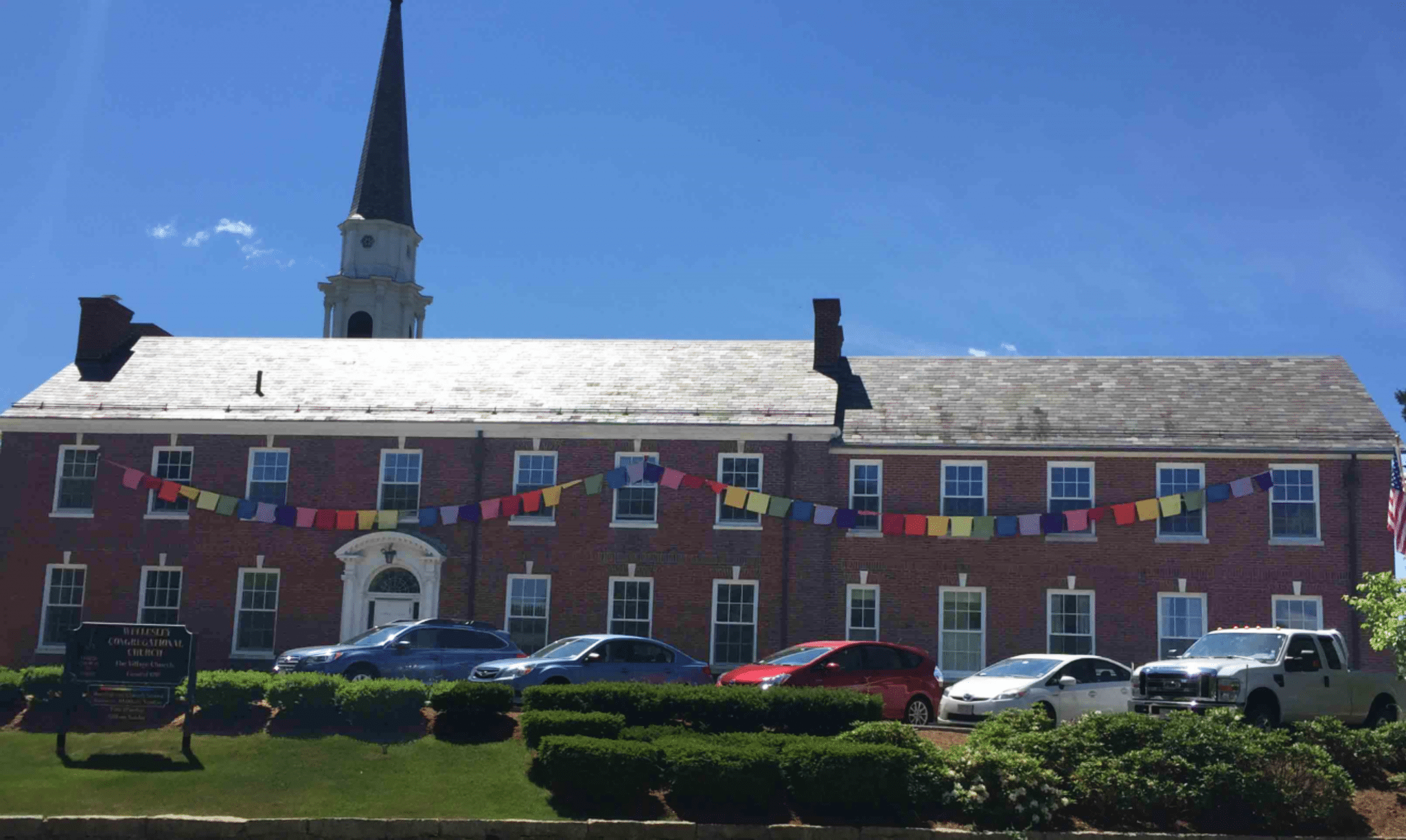 Prayer flags across the facade of the Central St. side of Wellesley Village Church. Photo credit: Village Church