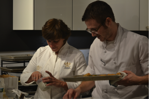 Barbara Lynch and a staff member preparing asparagus wrapped in phyllo pastry