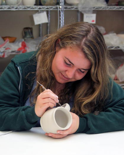 Intensive Ceramics student Michaela Osborn putting finishing touches on a mug