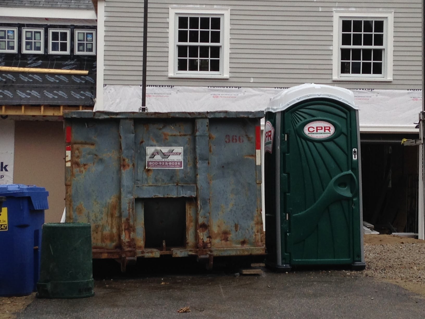 Here, the battered dumpster stands in contrast to the newness of the Port-a-potty and the renovated house itself.