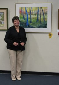 "Evelyn Bernal in front of her painting entitled ""New Light."