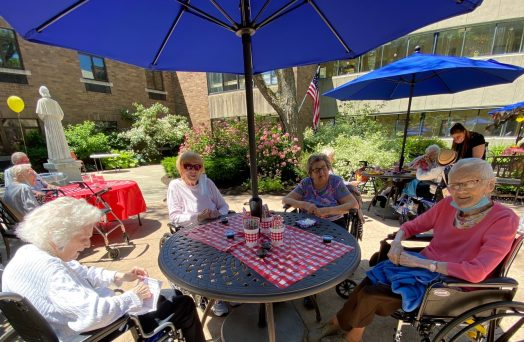 Residents enjoying a sunny afternoon cookout in the courtyard of the Elizabeth Seton Residence.